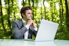 坐在办公桌的想法的商人工作在便携式计算机在绿色森林公园 自由职业者用在下巴workin的手 库存图片