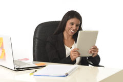 坐在办公计算机书桌微笑的西班牙女实业家愉快使用数字式片剂 库存图片