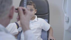 坐在医生眼医专业眼科医生椅子的英俊的混血儿男孩画象检查 股票录像