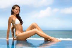 坐在华美的游泳池前面的泳装的妇女 免版税库存照片