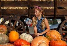 坐在南瓜之间的愉快的学校女孩在地方农夫市场上在晴朗的秋天天 免版税库存图片