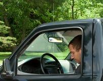 坐在卡车的年轻成人人在公园 免版税库存照片