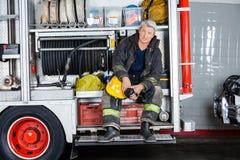 坐在卡车的确信的消防员在消防局 免版税库存照片