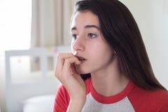 坐在卧室尖酸的钉子的十几岁的女孩 免版税库存照片