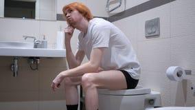 坐在卫生间洗脸台的想法的红头发人人 免版税库存图片