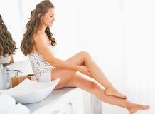 坐在卫生间里和检查腿皮肤软性的愉快的妇女 免版税库存照片