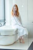 坐在卫生间里的浴巾的红头发人妇女 免版税库存照片