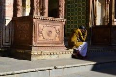 坐在印度寺庙附近的印地安人 免版税库存图片