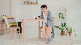 坐在厨房佩带的睡衣和浏览互联网的愉快的妇女 深色的女孩使用智能手机并且喝咖啡 图库摄影