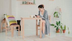 坐在厨房佩带的睡衣和浏览互联网的愉快的妇女 深色的女孩使用智能手机并且喝咖啡 库存照片