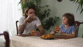 坐在厨房用桌里和吃与热奶咖啡的两个兄弟新月形面包 更老和弟弟聊天和 股票录像