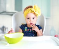 坐在厨房空的桌上的孩子 库存照片