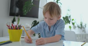坐在厨房里的一件蓝色T恤杉的一个男孩在桌上画做家庭作业学龄前训练的铅笔 影视素材