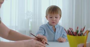 坐在厨房里的一件蓝色T恤杉的一个男孩在桌上画标志 股票录像
