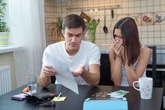 坐在厨房里的一对年轻夫妇计划和分析家庭预算 财政困难,消极情感 免版税库存图片