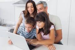 坐在厨房里的家庭使用他们的膝上型计算机 库存照片