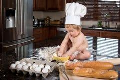 坐在厨房里的小贝克 库存图片