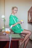 坐在厨房里的年轻白肤金发的妇女 免版税库存照片
