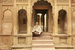 坐在古庙附近的男性教士在沃林达文印度 库存图片