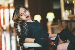 坐在古色古香的扶手椅子的华美的丝绸礼服的典雅的年轻美丽的妇女 库存照片