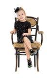 坐在古色古香的椅子的小女孩 库存图片