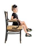 坐在古色古香的椅子的小女孩 免版税库存照片