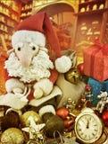 坐在古色古香的玩具中的圣诞老人在警报旁边 库存照片