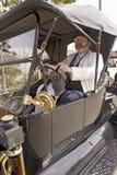 坐在古董车之后轮子的驱动器  库存图片