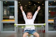 坐在台车的微笑的小孩女孩在家庭购物期间在市场上 免版税库存图片
