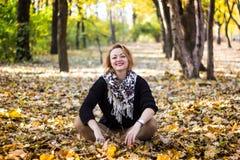 坐在叶子的愉快的少妇在秋天公园 免版税图库摄影