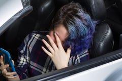 坐在司机汽车边位子的沮丧的十几岁的女孩  库存图片