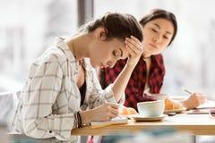 坐在咖啡休息和写在笔记本,工作午餐的女孩 免版税库存图片