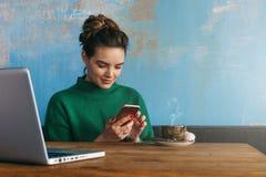 坐在咖啡店和用途智能手机的桌上的年轻微笑的女商人 在桌上是膝上型计算机和咖啡 库存照片