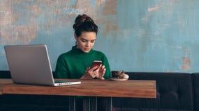 坐在咖啡店和用途智能手机的桌上的绿色衬衣的年轻女商人 免版税库存图片