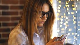 坐在咖啡店在木桌上和使用智能手机的少妇 影视素材