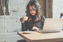 坐在咖啡店在木桌,饮用的咖啡上和使用智能手机的少妇 在桌上是膝上型计算机 女孩浏览的实习生 图库摄影