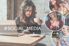 坐在咖啡店在木桌,饮用的咖啡上和使用智能手机的少妇 在桌上是膝上型计算机 库存照片