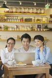 坐在咖啡店的三个朋友,看照相机 免版税图库摄影
