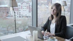 坐在咖啡店的少妇在木桌上 在桌上是灰色铝膝上型计算机 写博克的女孩,浏览互联网 股票视频