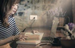 坐在咖啡店的少妇在木桌阅读书 库存照片