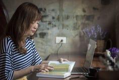 坐在咖啡店的少妇在木桌阅读书 免版税库存图片
