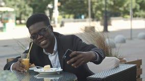 坐在咖啡店的微笑的年轻商人使用手机,采取selfie 库存照片