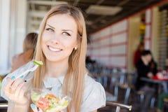 坐在咖啡店的特写镜头画象快乐的美丽的白肤金发的妇女举行一可口沙拉愉快微笑在餐馆 库存照片
