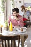 坐在咖啡店的现代年轻人 库存图片