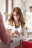 坐在咖啡店的现代妇女 免版税库存照片