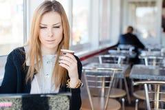 坐在咖啡店饮用的咖啡和工作在便携式计算机个人计算机的美丽的年轻白肤金发的女商人 免版税库存照片