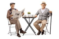 坐在咖啡桌上和看凸轮的两个年长人 库存图片