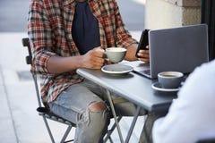坐在咖啡馆之外的两个成人人低部分庄稼  图库摄影