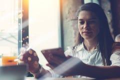 坐在咖啡馆和使用手机的英俊的妇女读在电子邮件的新的inbox信 免版税库存图片