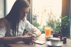 坐在咖啡馆和使用手机的英俊的妇女读每日新闻传递 库存照片